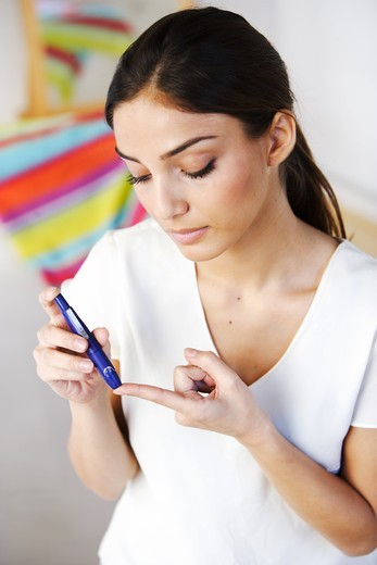 A diabetic person is checking her blood sugar level (self glycemia). A drop of blood obtained with a pen-like lancing device is placed on a test stick and analysed with blood glucose tester (glucometer). : Stock Photo