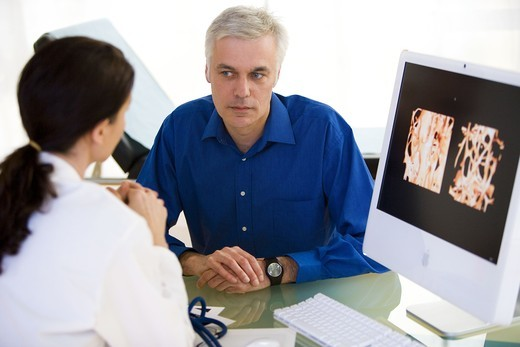 Doctor showing a patient the effect of osteoporosis on the bone structure of a vertebra. : Stock Photo