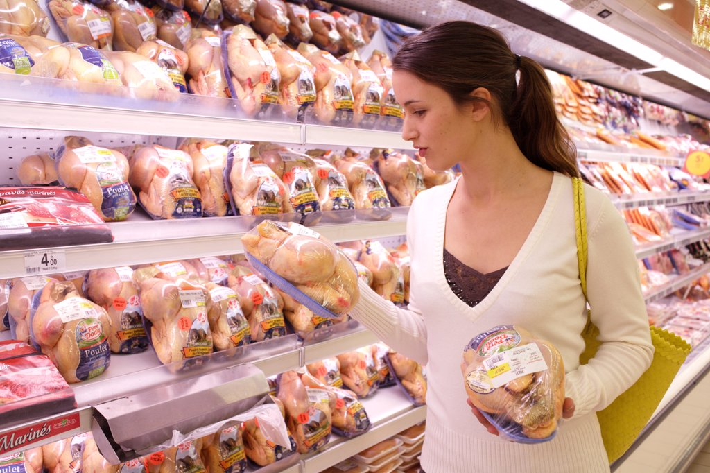Woman shopping in the poultry section in supermarket. : Stock Photo