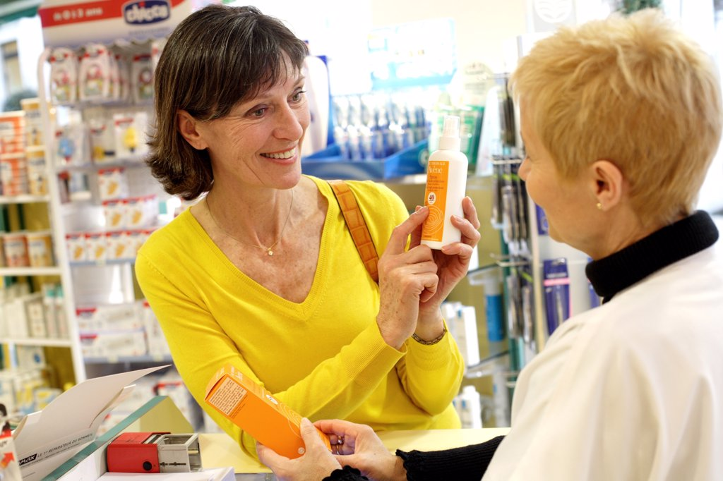 Pharmacist showing a customer different sunblocs. : Stock Photo