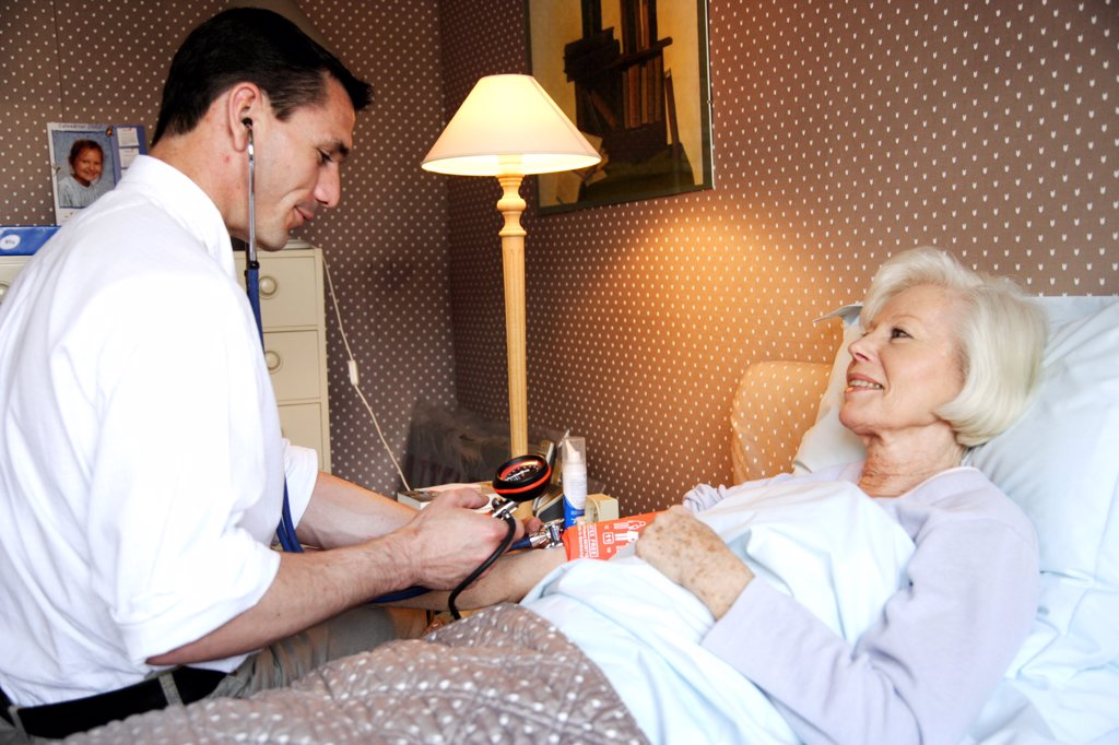 Doctor checking the blood pressure of a patient. : Stock Photo