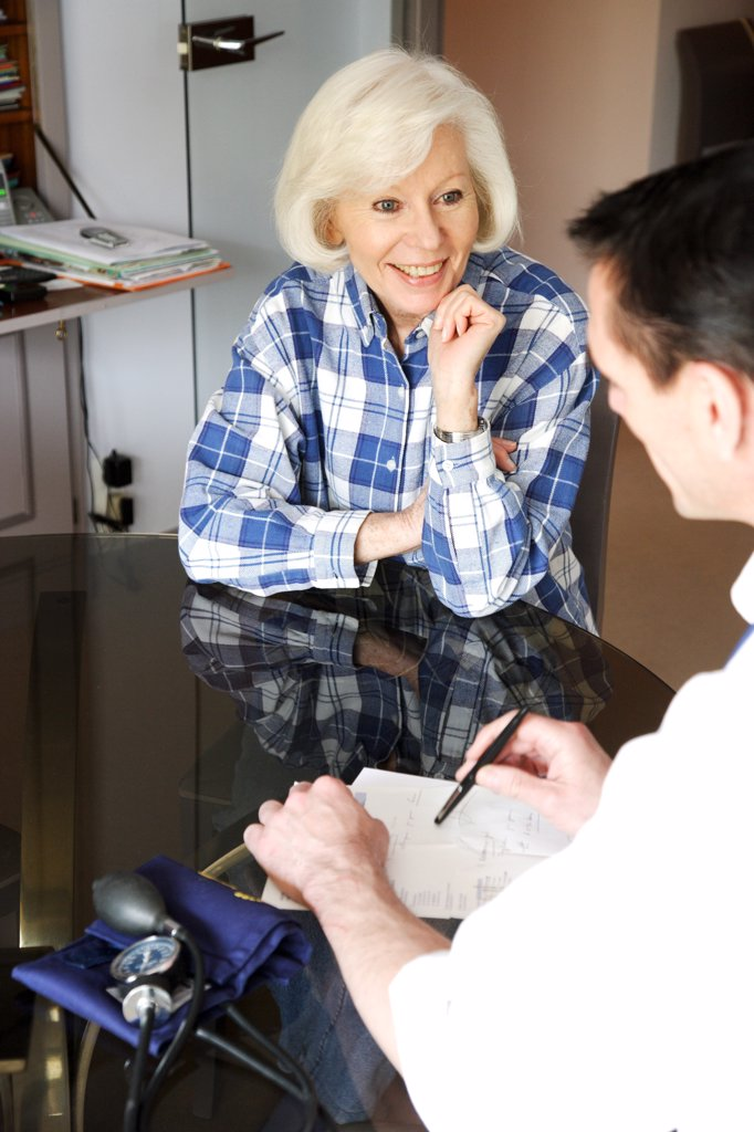 General practitioner writing a medical prescription after home visit. : Stock Photo