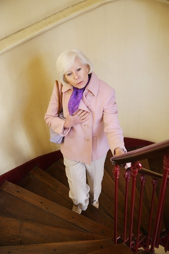 Elderly woman climbing up the stairs. : Stock Photo