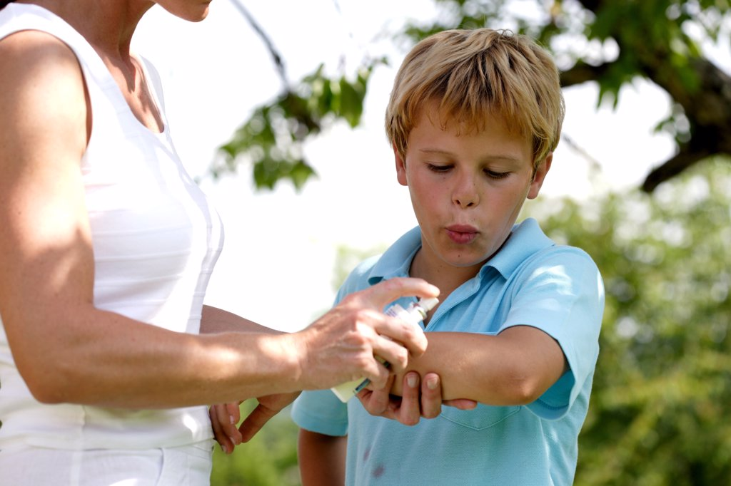 Woman applying spray on itchy skin of her son following insect bite. : Stock Photo