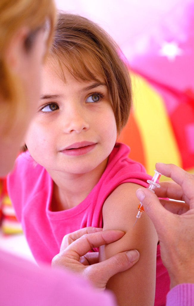 6 years old girl receiving a vaccination. : Stock Photo