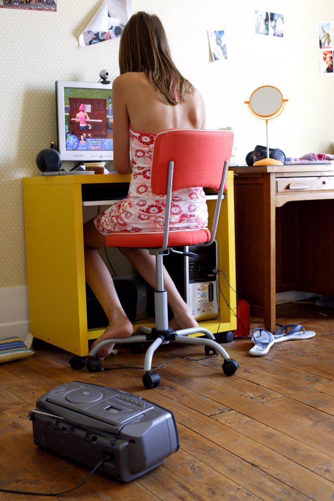 Stock Photo: 4269-7025 Teenage girl using her computer in her bedroom.