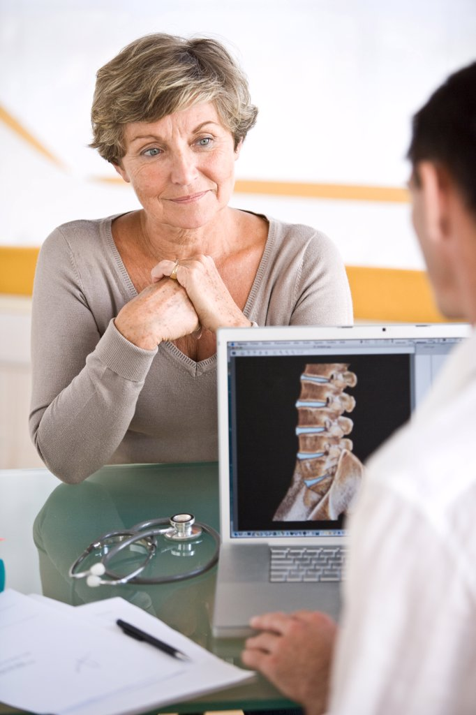 Stock Photo: 4269-7517 Doctor discussing backbone 3D CT scan with a patient.