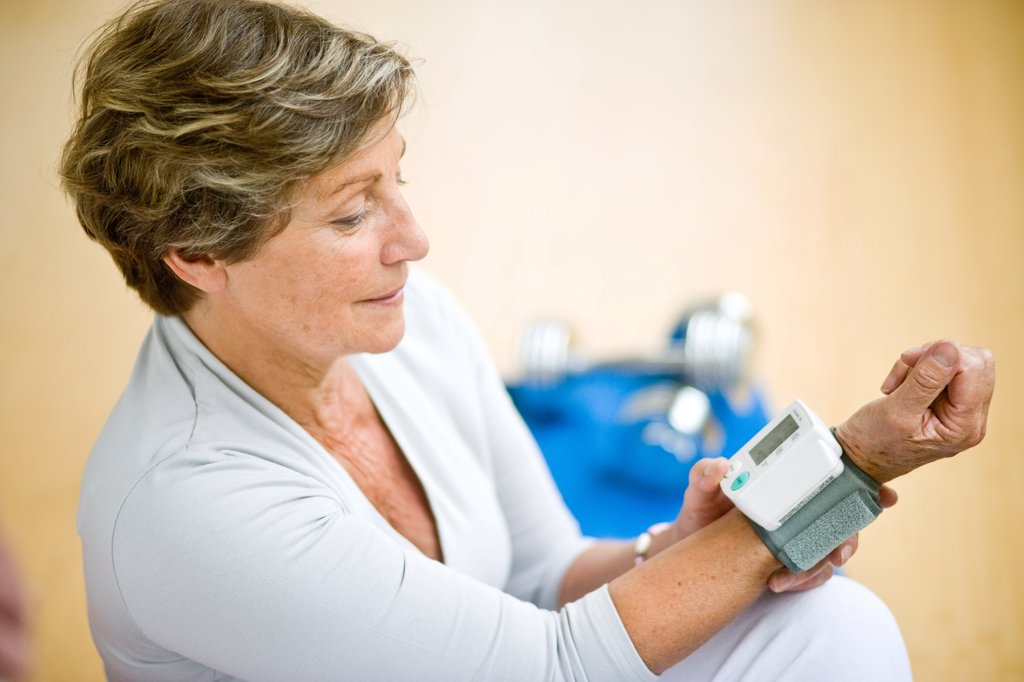 Senior woman taking her blood pressure with a portable blood pressure monitor. : Stock Photo