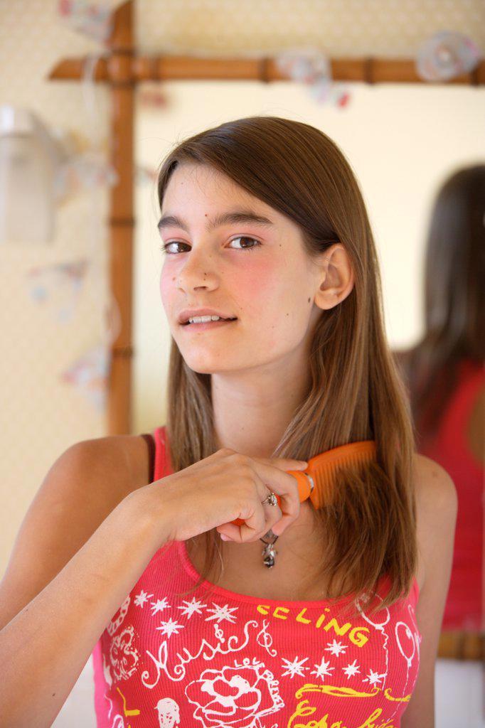 Stock Photo: 4269-7700 Teenage girl doing her hair.