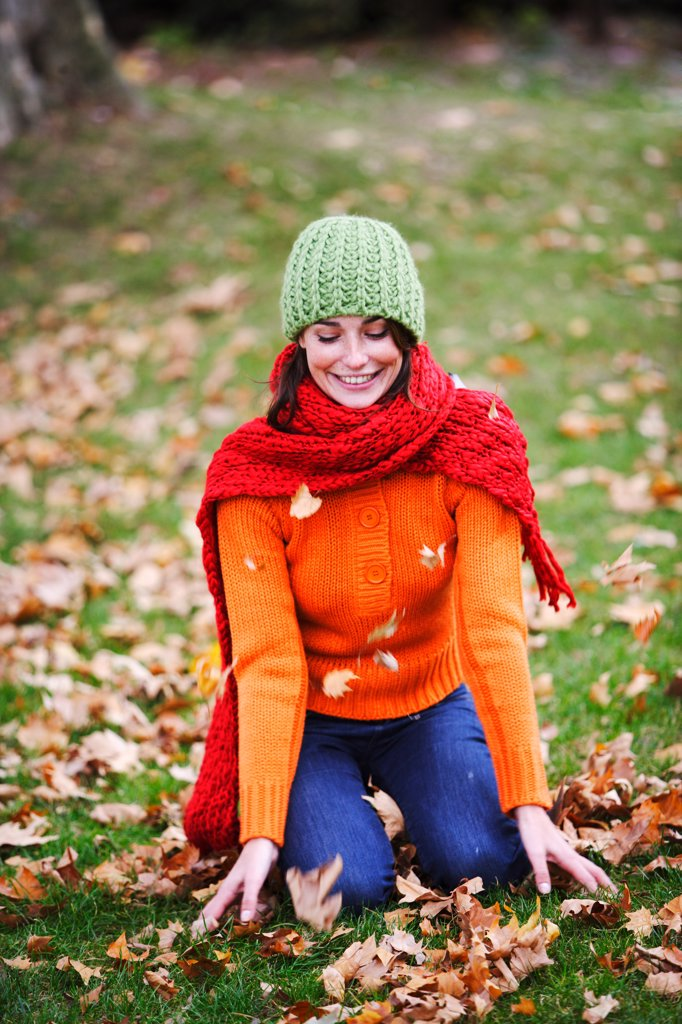 Woman with dead leaves in autumn. : Stock Photo