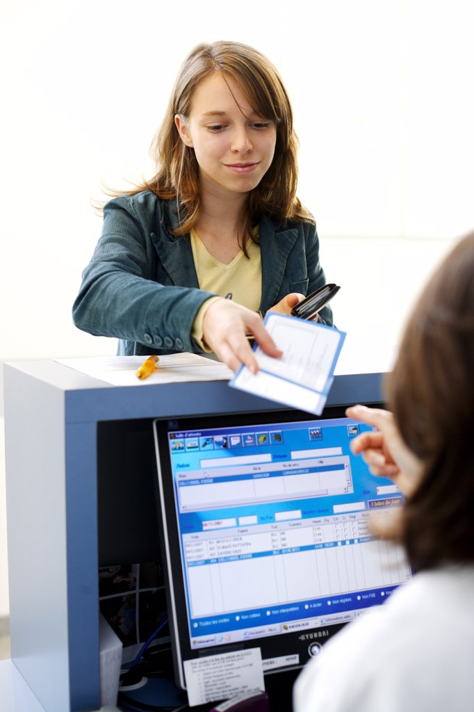 Woman giving documents at reception desk. : Stock Photo