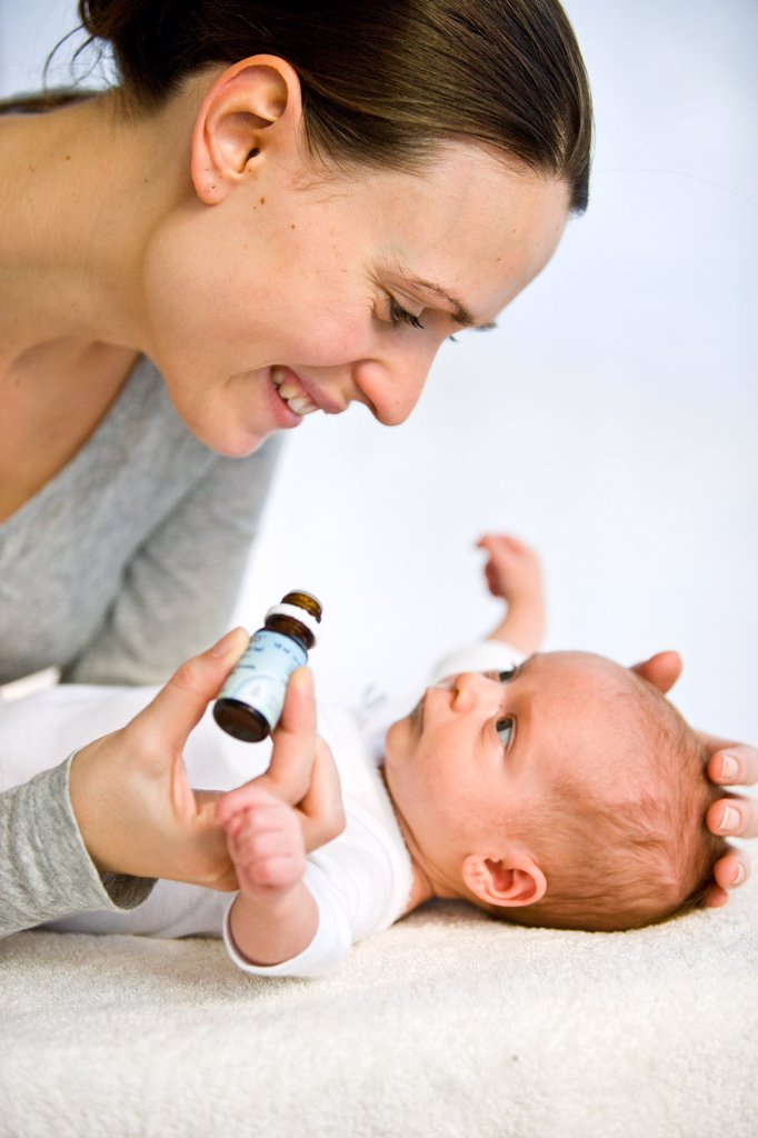 A mother is giving drops of vitamin D to her one month old baby. : Stock Photo