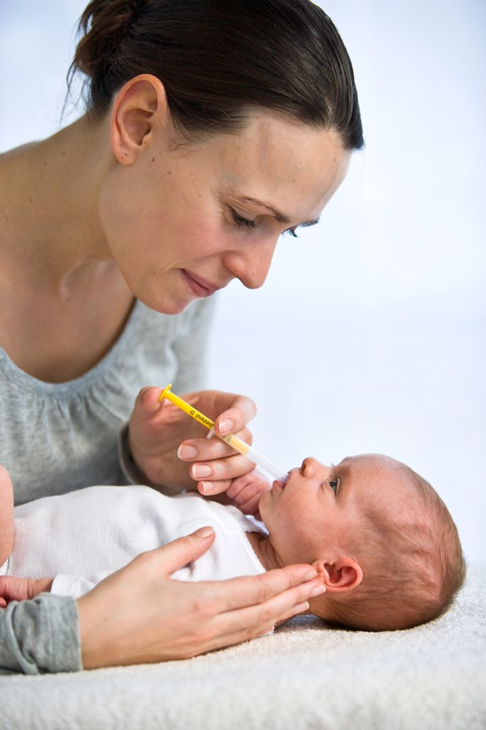 Stock Photo: 4269-8351 Mother giving her one month old baby vitamin D with a pipette.