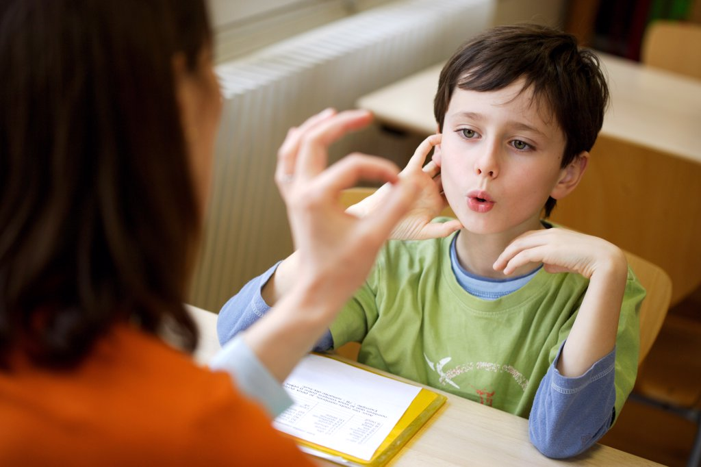 8 years old boy during speech therapy cession. : Stock Photo