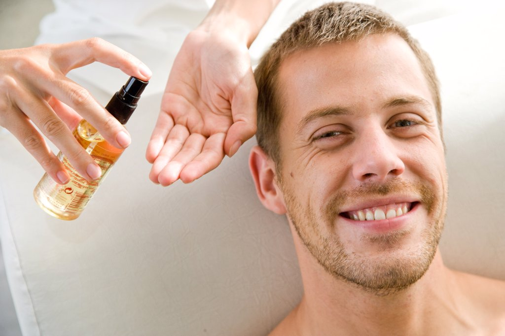 Man receiving oil face care. : Stock Photo