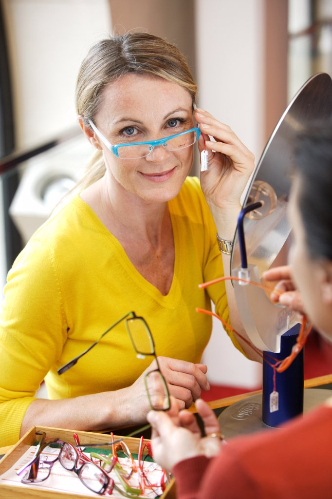 Woman trying on prescription glasses in opticians. : Stock Photo