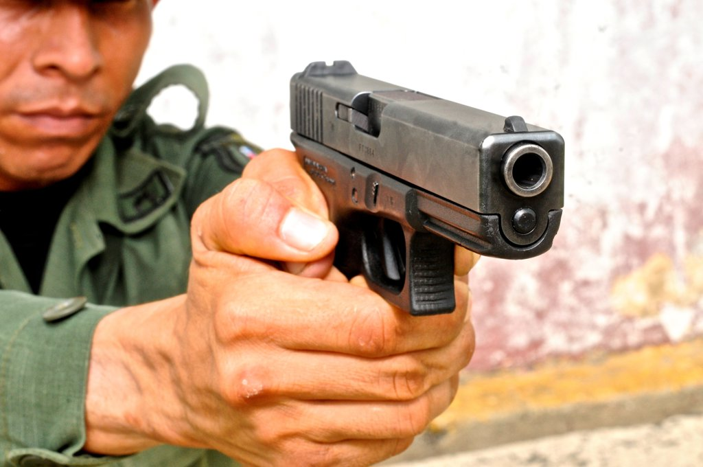 Uniformed police officer aiming a pistol at a tactical and firearms training course at the Panamanian National Police force academy, Panama : Stock Photo