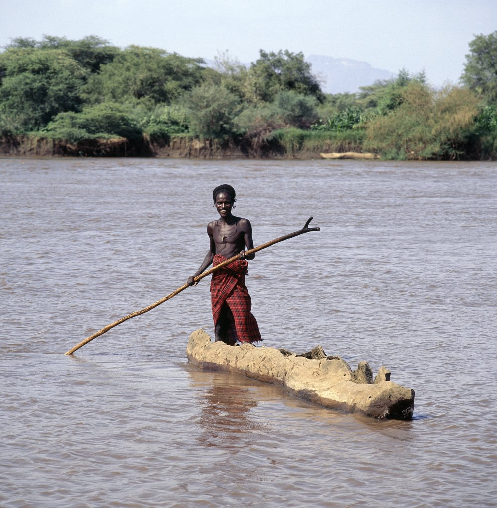 Stock Photo: 4272-10079 A Dassanech man poles a dug-out canoe across the muddy waters of a tributary of the Omo River in its delta near Lake Turkana.  The Omo has one of the largest inland deltas in the world and is home to a large section of Dassanech people who speak a language of Eastern Cushitic origin.