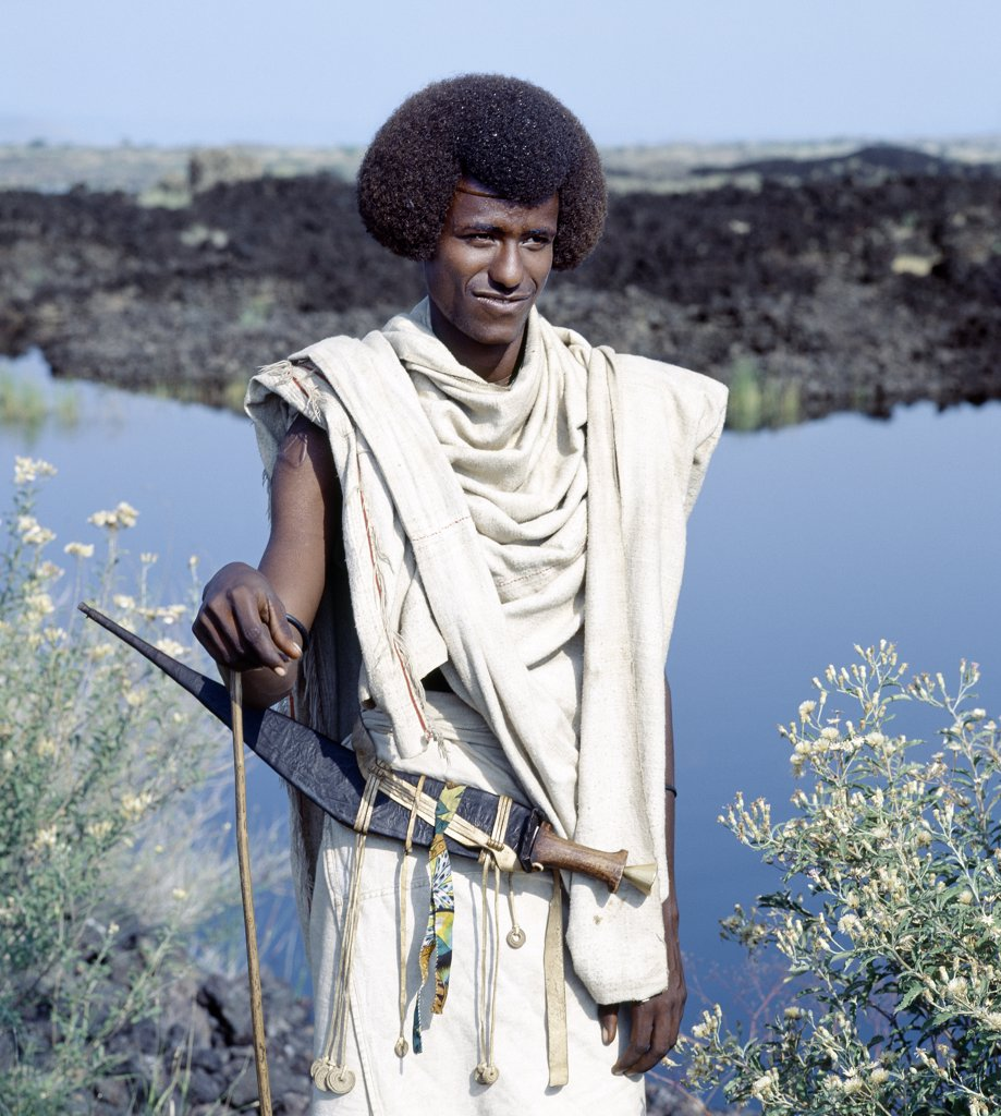 Stock Photo: 4272-10227 A Kereyu man with his fuzzy, well-oiled hair fashioned in a semi-circular shape.  His long curved dagger is typical of his tribe.  He wears unbleached cloth made from local cotton.