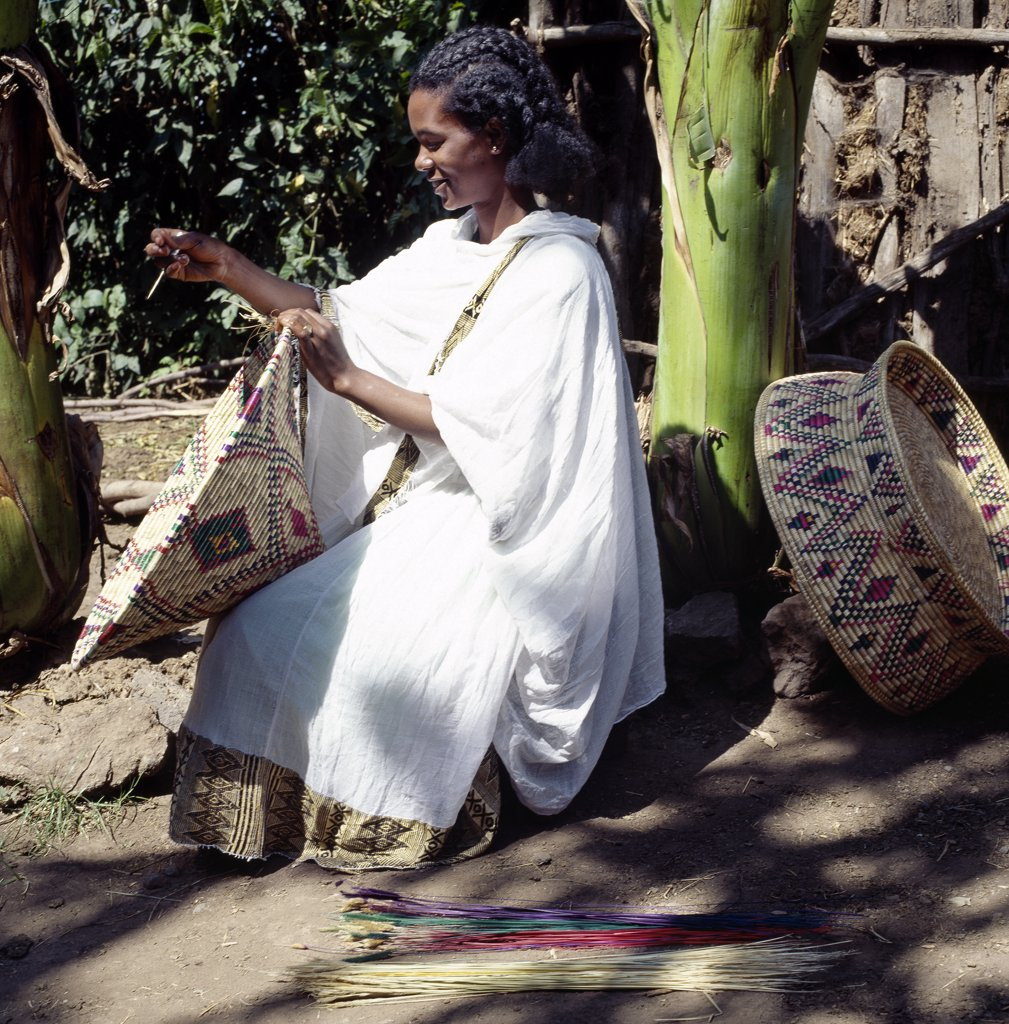 Stock Photo: 4272-10238 A young Amhara lady weaves a traditional food basket from dried grasses. These large colourful baskets are used for serving injera, a fermented, bread-type pancake, which is the country's national dish.She is wearing the national dress of Ethiopia - a shamma. This garment is made of homespun cotton with a finely woven and often brightly coloured border.