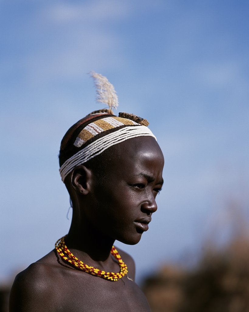 Stock Photo: 4272-10473 A young Dassanech boy with an elaborate clay hairdo and headband of beads at his village in the Omo Delta.  Much the largest of the tribes in the Omo Valley numbering around 50,000, the Dassanech (also known as the Galeb, Changila or Merille) and Nilotic pastoralists and agriculturalists.
