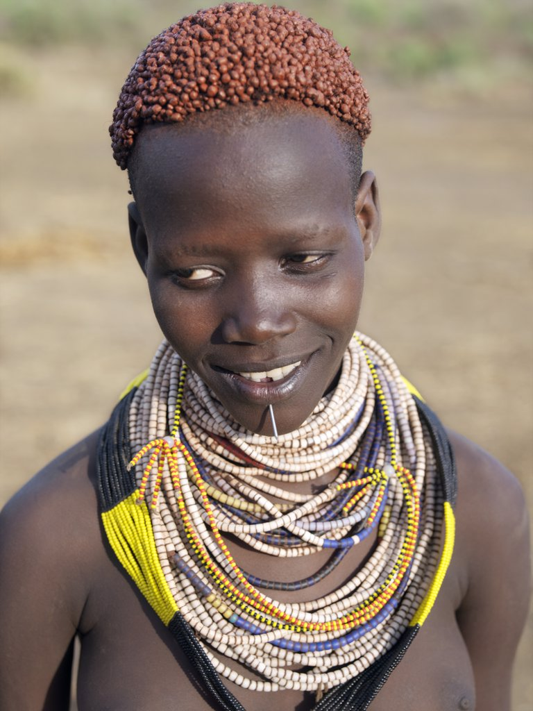 A Karo girl in all her finery.  It is a Karo tradition for girls and young women to pierce a hole below the lower lip in which they place a thin piece of metal or a nail for decoration. The Karo are a small tribe living in three main villages along the lower reaches of the Omo River in southwest Ethiopia. : Stock Photo