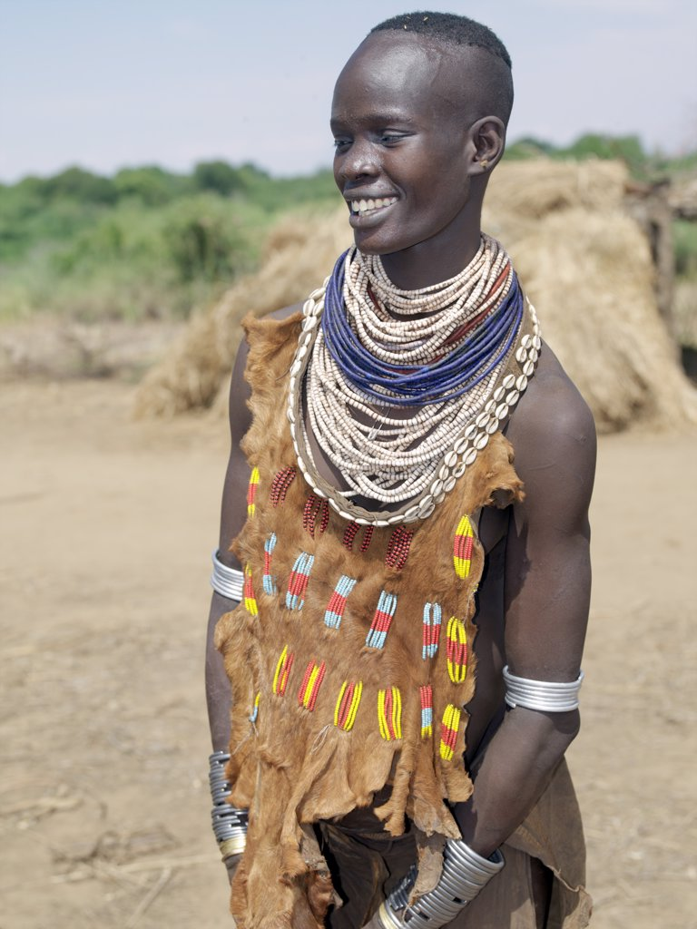 Stock Photo: 4272-10685 A Kwegu woman in an attractively decorated leather garment. The Kwegu are the smallest tribe living on the banks the Omo River in southwest Ethiopia.
