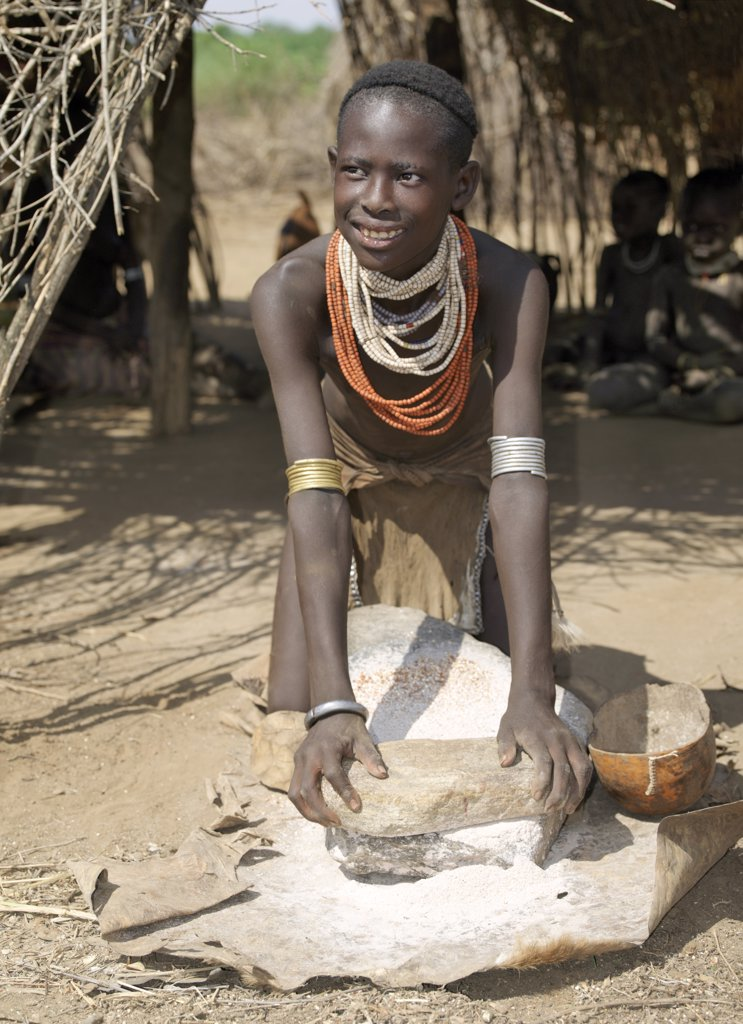 A Kwegu girl grinds sorghum using a flat grinding stone. The Kwegu are the smallest tribe living on the banks the Omo River in southwest Ethiopia. : Stock Photo