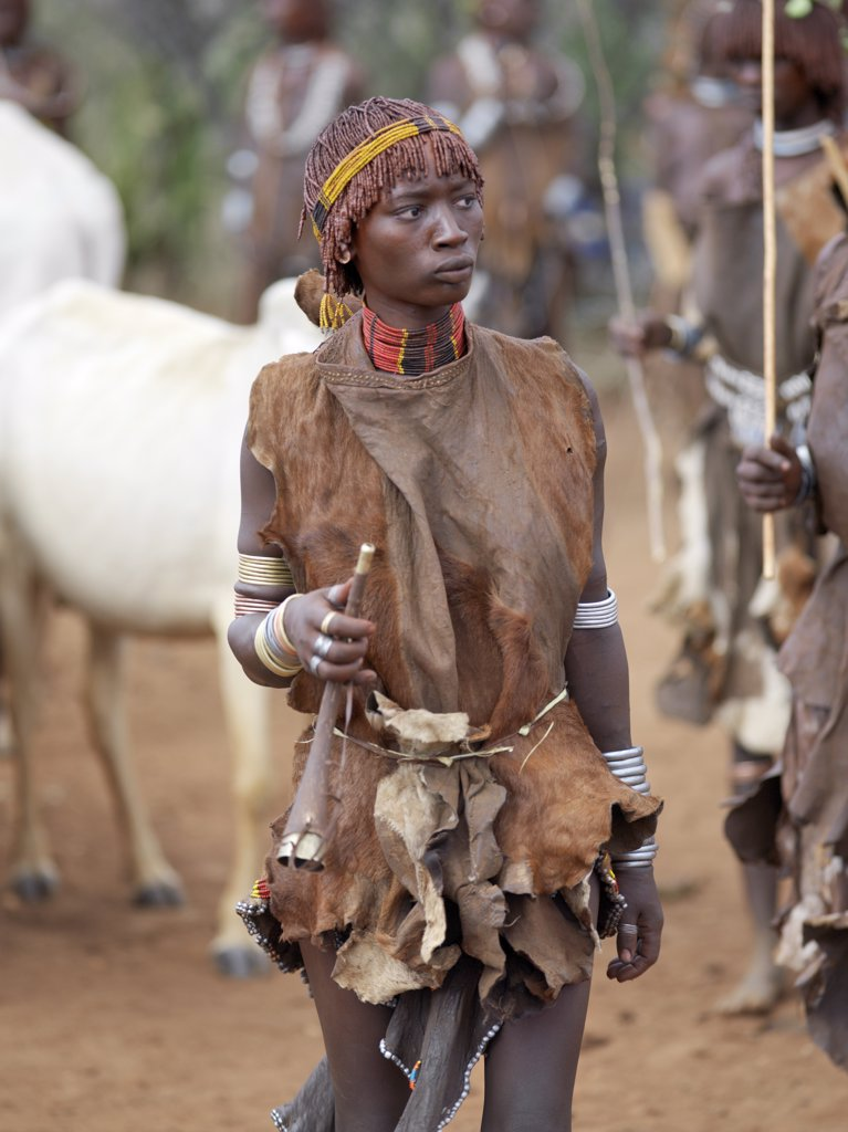A Hamar woman holds a tin trumpet at a Jumping of the Bull ceremony. The Hamar are semi nomadic pastoralists of Southwest Ethiopia whose women wear striking traditional dress and style their red ochred hair mop fashion. : Stock Photo