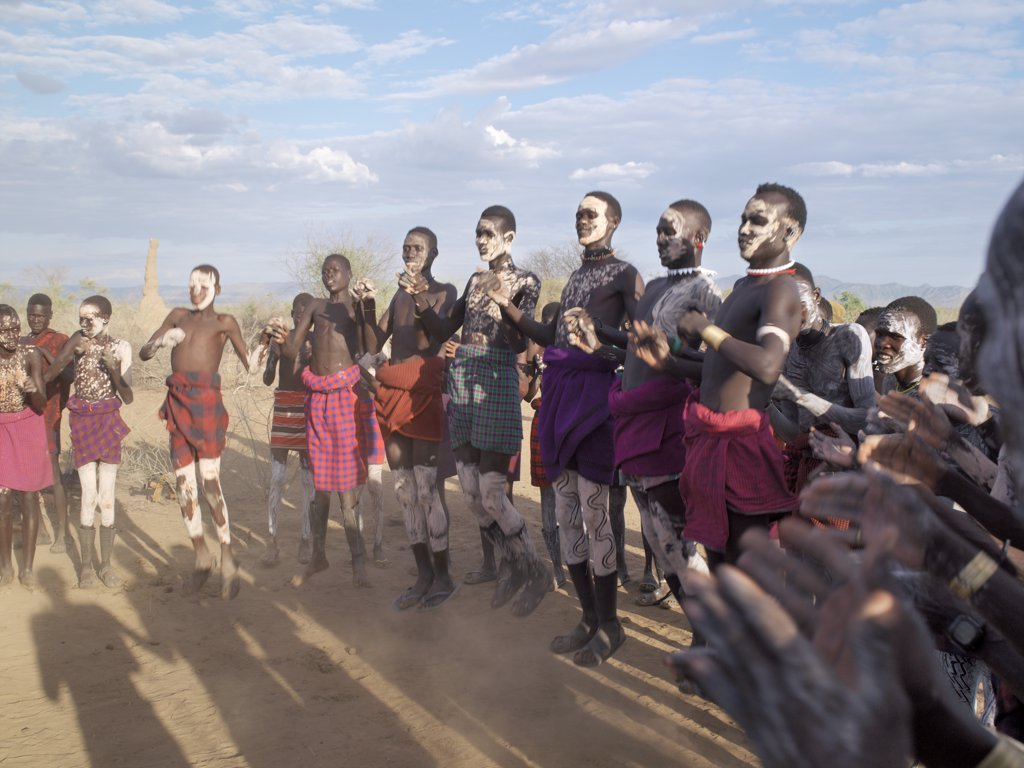 In the late afternoon, Nyagatom villagers enjoy singing and dancing.  As groups of men take centre stage to jump high in the air, women and girls sing, clap to a rhythm, and move slowly towards the men.  Children enjoy the excitement in the background. The Nyagatom are one of the largest tribes and arguably the most warlike people living along the Omo River in Southwest Ethiopia. : Stock Photo