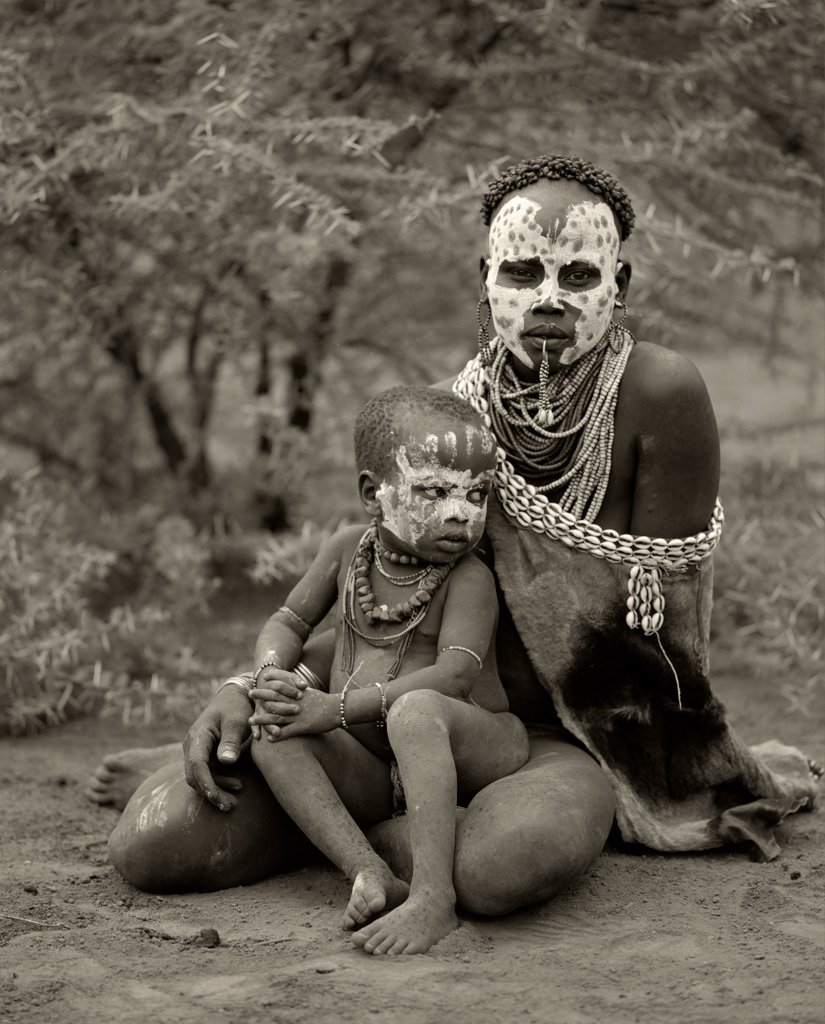 Stock Photo: 4272-10858 Ethiopia, Omo Delta.  A woman from the Karo tribe, famous for their face painting, with her child.