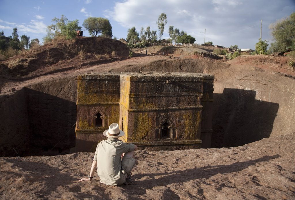 Stock Photo: 4272-10872 Ethiopia, Lalibela, Bet Giyorgis. A tourist gazes at the rock-hewn church of Bet Giyorgis. (MR)