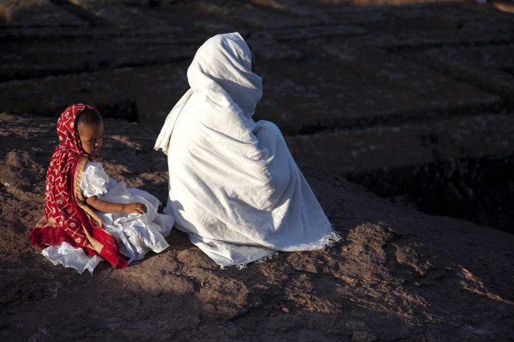 Stock Photo: 4272-10885 Ethiopia, Lalibela. A woman prays by Bet Giyorgis, whilst her daughter loses concentration.