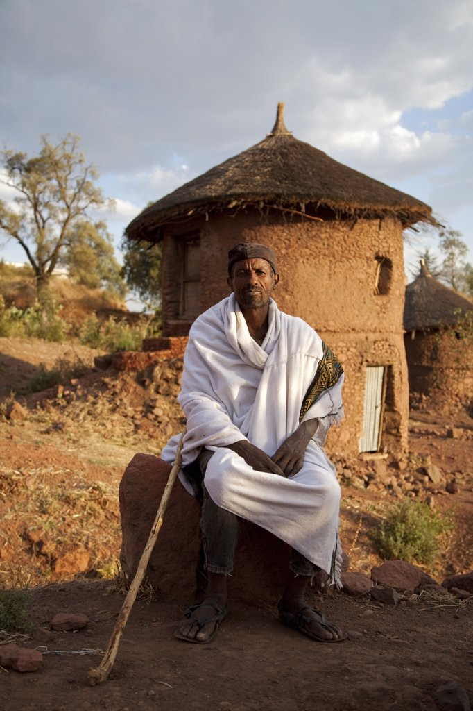 Ethiopia, Lalibela. A Christian man sits in front of his house in Lalibela at sunset. : Stock Photo
