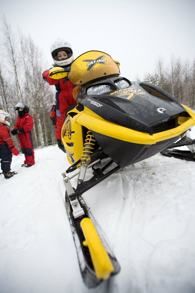 Finland, Pielinen region of North Koralia in Finnish Lapland. Girl on snowmobile (or skidoo) safari. (MR) : Stock Photo