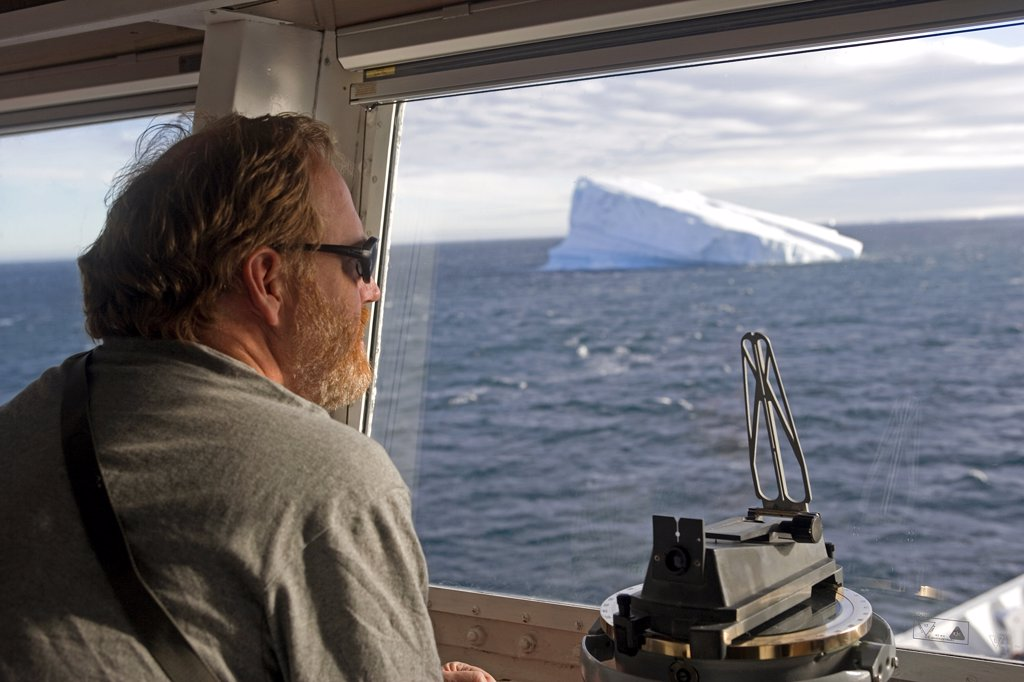 Antarctica, Antarctic Sound. Expedition leader Dr Peter Cary on the bridge of the cruise ship MS Discovery overlooking the icebergs of the Antarctic Sound. : Stock Photo
