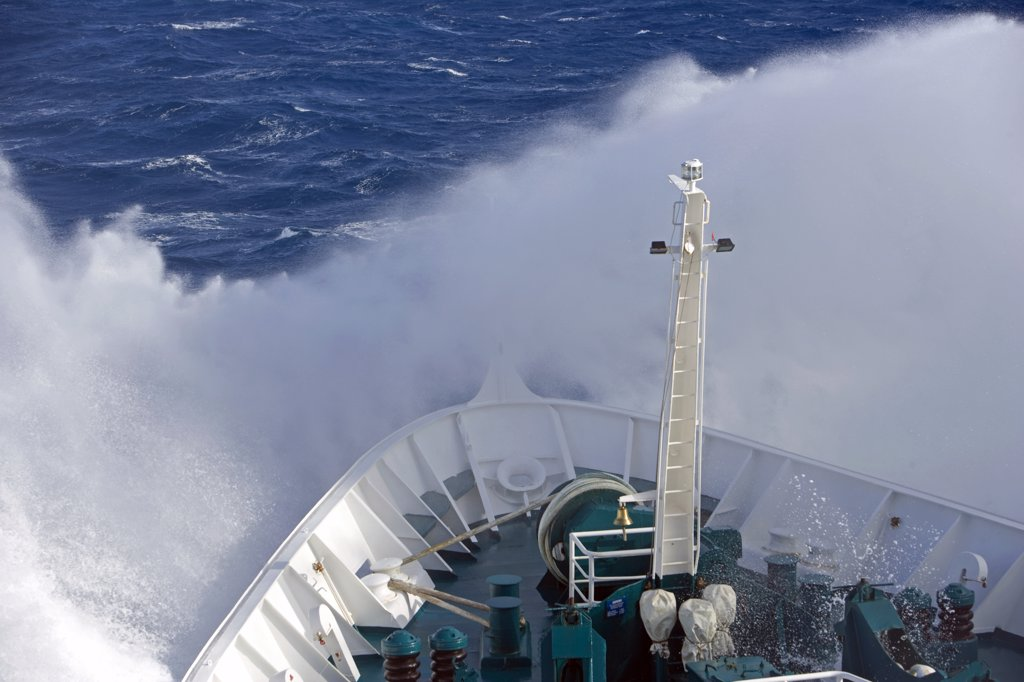 Antarctica, Antarctic Peninsula, Drakes Passage. Running into heavy seas, the bow of the expedition ship MV Discovery cut a path through the deep blue sea separating the southern continent from South America. : Stock Photo