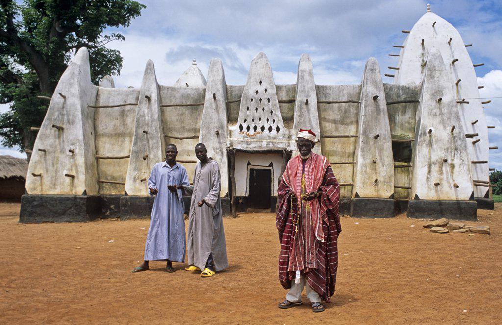 Ghana, Northern Region, Larabanga. The Imam and two young muslims stand outside the thirteenth century mosque at Larabanga, near Mole National park. : Stock Photo