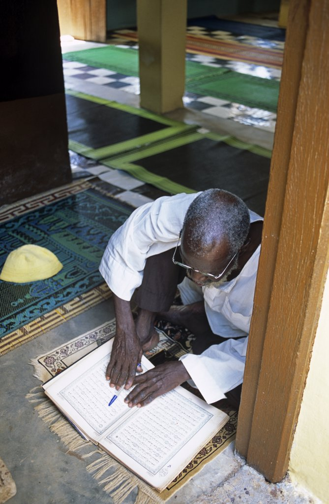 Stock Photo: 4272-12576 Ghana, Northern region, Tamale. A Muslim prays and reads the Quran at a Mosque in Tamale during Ramadan.