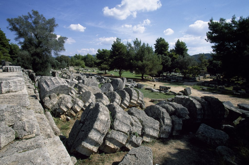 Stock Photo: 4272-12669 Fallen pillars mark the site of Ancient Olympia's Temple of Zeus, a massive Doric temple constructed in 460BC that housed an enthroned stataue of the god made from wood, ivory and gold. The famous sculptor, Peidias, created the statue and you can still see the remains of his workshop nearby.