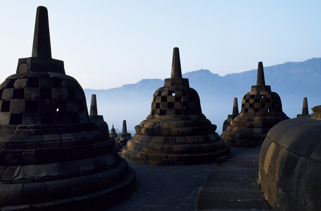 Stock Photo: 4272-13311 Latticed stupas on upper terraces, Borobodur temple, Java, Indonesia. Ranking with Pagan and Angkor as one of the greatest Southeast Asian monuments, Borobodor is an enormous construction standing majestically on a hill overlooking lush green fields and distant hills, 42km northwest of Yogyakarta.