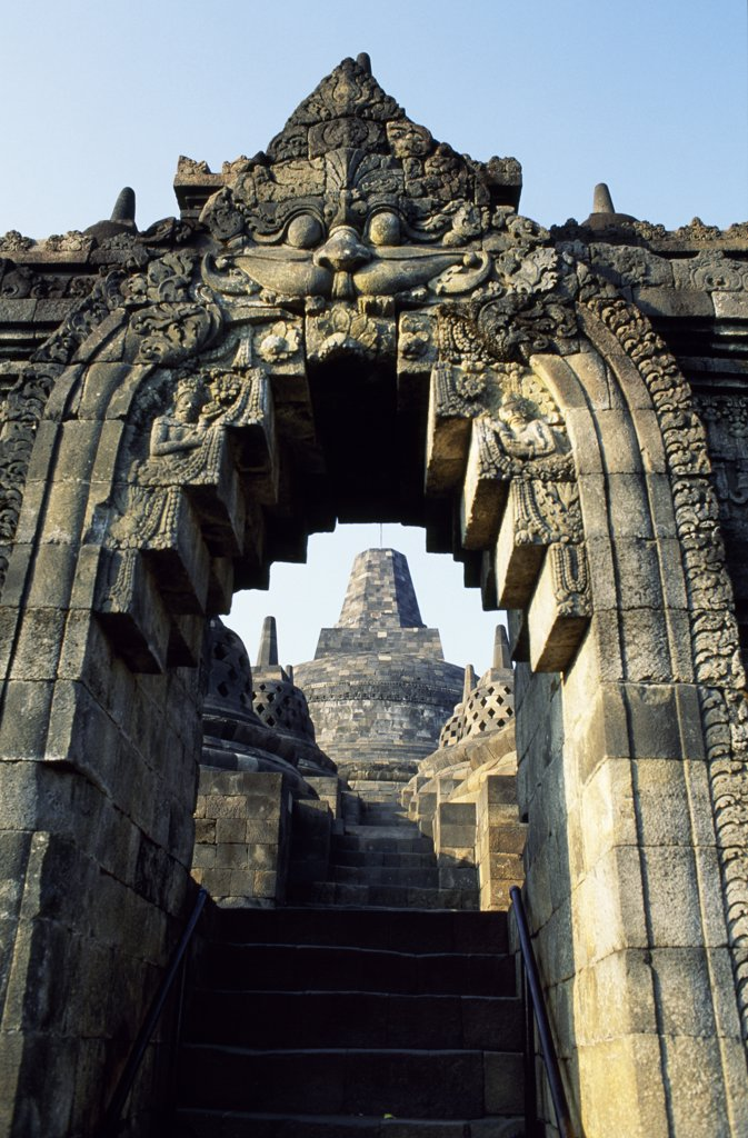 Stock Photo: 4272-13315 View to Grand Stupa from lower terrace through sculpted archway, Borobodur temple, Java, Indonesia. Ranking with Pagan and Angkor as one of the greatest Southeast Asian monuments, Borobodor is an enormous construction standing majestically on a hill overlooking lush green fields and distant hills, 42km northwest of Yogyakarta.