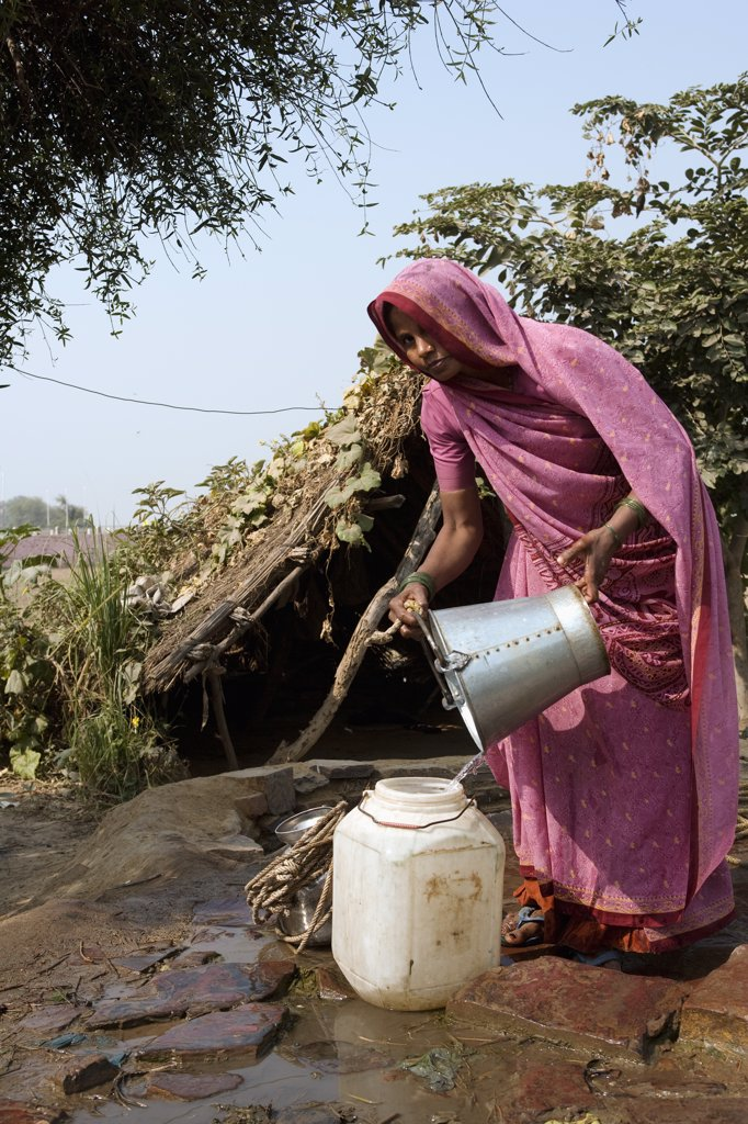 India, Rajasthan, Rohet.  Without running water in their homes, the village well and water pump become a meeting point for the women of the communities. : Stock Photo