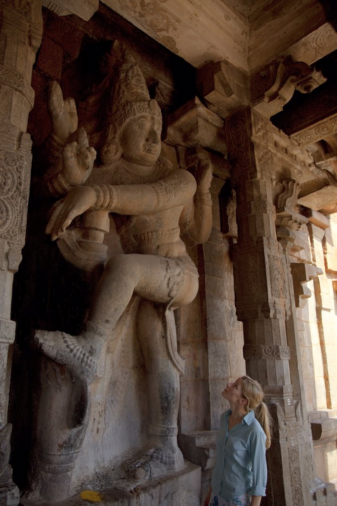 Stock Photo: 4272-14276 India, Thanjavur. A tourist marvels at the size of a carving of a deity at the Brihadeeswarar Temple. MR.