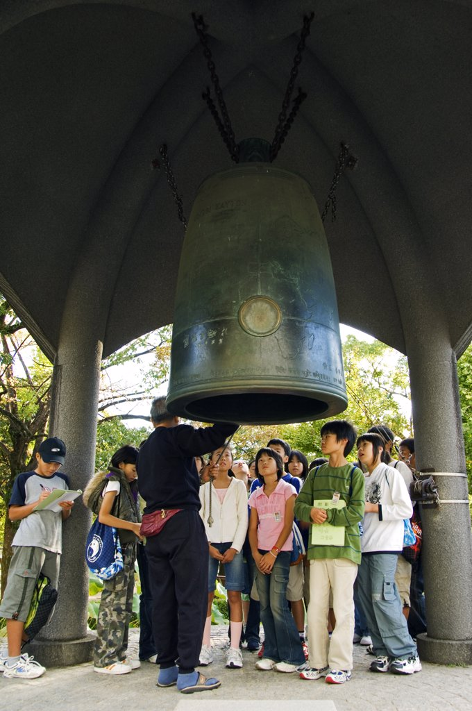Stock Photo: 4272-15668 Japan, Honshu Island, Hiroshima Prefecture, Hiroshima City, Hiroshima Peace Memorial Park. Students being educated about WWII and the Peace Bell.