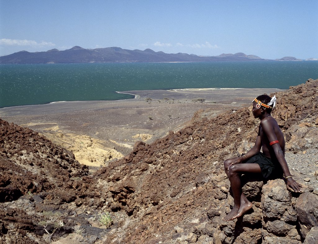 Stock Photo: 4272-16260 A young Turkana man looks out over Lake Turkana, often referred to as the Jade Sea due to the colour of its alkaline water.  The barren, windswept country at this southeast corner of the lake is strewn with basalt lava boulders. 160 miles long and between 8 and 27 miles wide, Lake Turkana is one of the oldest and largest lakes of Africas Great Rift Valley system.