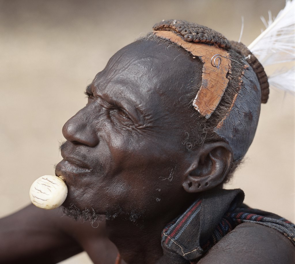 Stock Photo: 4272-16299 Turkana elders wear decorative ivory lip ornaments, secured in position by a spigot which is inserted in a hole pierced below the man's lower lip after initiation.  This singular form of decoration was once widespread but is rarely seen today. Likewise, the traditional clay hairdo is gradually dying out.