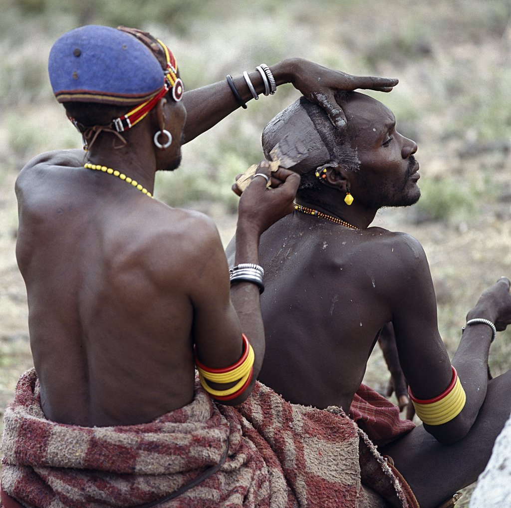 Stock Photo: 4272-16304 An expert hairstylist smears clay on the crown of a man's head, then fashions it into an elliptical bun before colouring it with natural  pigments.  The elliptical clay bun, so characteristic of the Turkana, is now dying out.