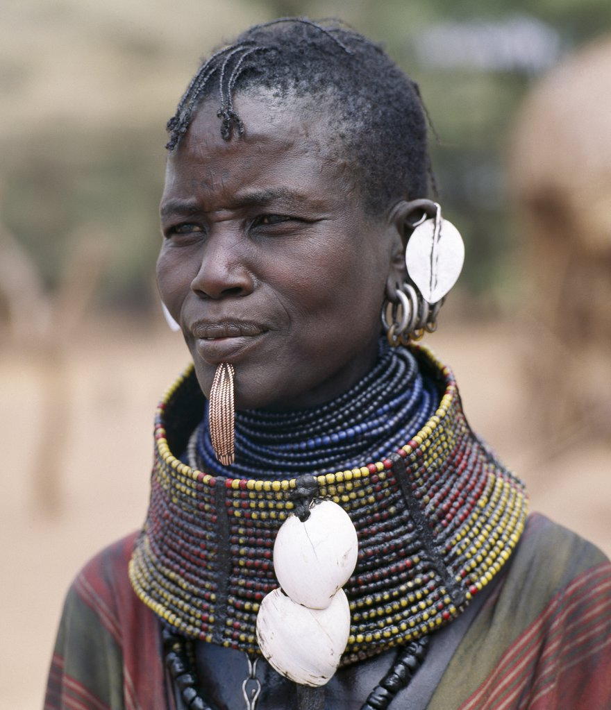 Stock Photo: 4272-16310 A Turkana woman wears all the finery of her tribe: brass lip plug, beaded collar decorated with bleached shells of the African land snail, leaf-like ear ornaments and metal earrings from which hang tiny rings of goat horn.