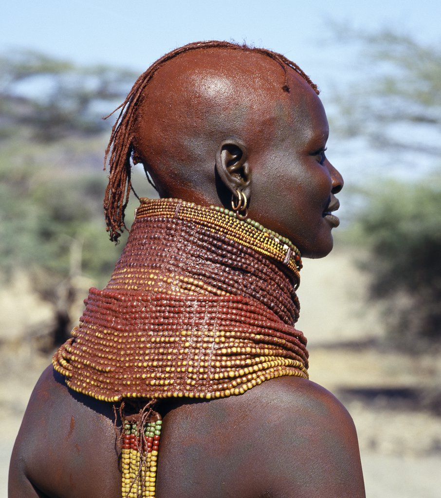 Stock Photo: 4272-16311 A Turkana girl's necklaces are well-oiled with animal fat and glisten in the sun. The use of red ochre has been copied from their Samburu neighbours and is not widespread. Occasionally, a girl will put on so many necklaces that her vertebrae stretch and her neck muscles gradually weaken. The partially shaven head is typical of Turkana women and girls.